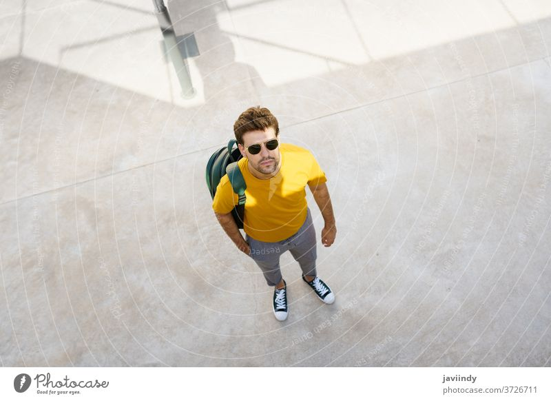 Top view of a male student on the university campus. man urban young backpack lifestyle person caucasian guy casual street background trendy stylish outside
