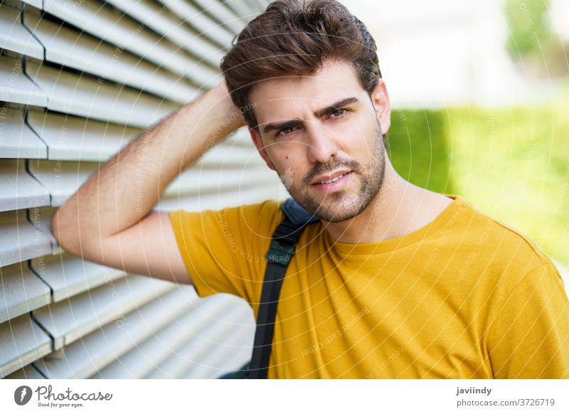 Young man with modern haircut in urban background male hairstyle student lifestyle cool person casual adult young outdoors street city trendy model caucasian