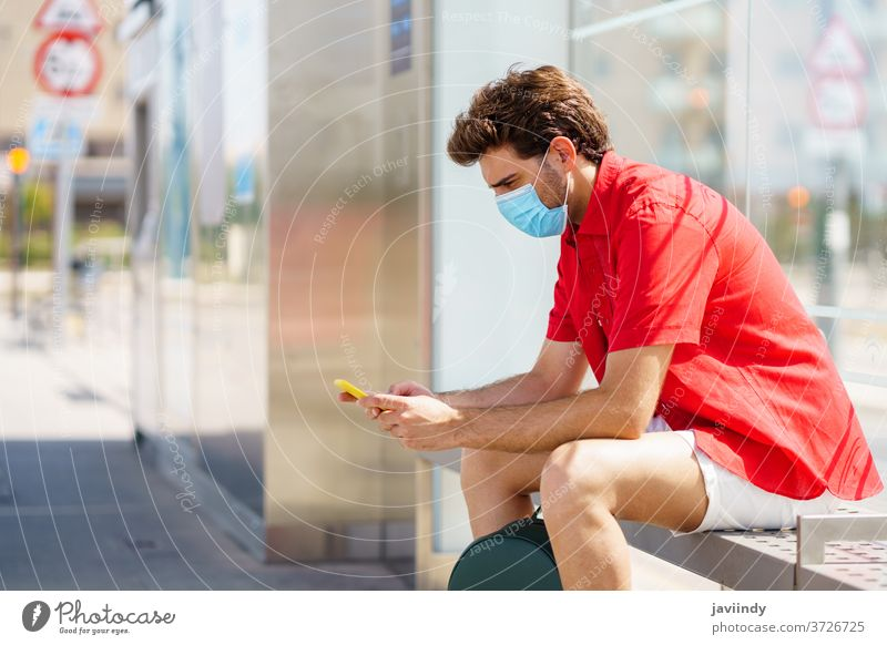 Young man wearing a surgical mask while waiting for a train at an outside station student tourism ecomobility traveler young male backpack lifestyle person