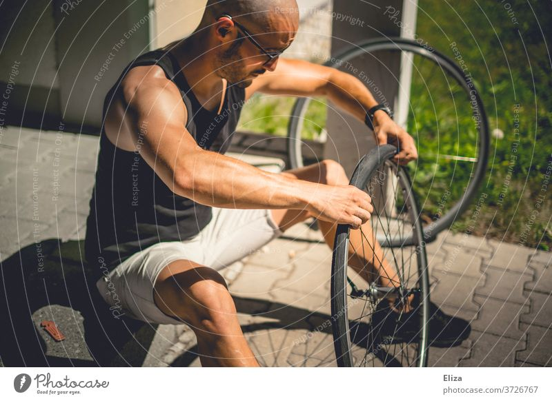 A man sits outside in the sun and pulls a bicycle coat onto the wheel of his bicycle after he has patched the tube Bicycle repair Coat Hose impeller wind Sun