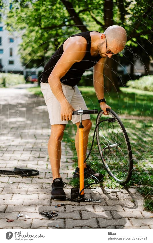A man pumps up the tire on his bicycle with a bicycle pump Air pump Tire Bicycle out Sun repair short pants Bald or shaved head do it oneself Wheel Athletic