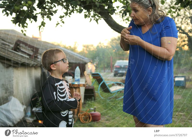 Woman speaking to child wearing a skeleton costume Portrait photograph Love Truth Trust Emotions Life Infancy Couple Family & Relations Grandmother