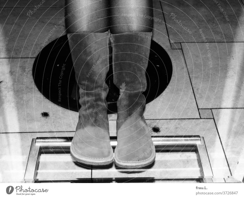 A pair of legs and boots admire each other in the full body mirror of the hairdressing salon. Hair Stylist Hairdresser Mirror floor tiles Tuft of hair