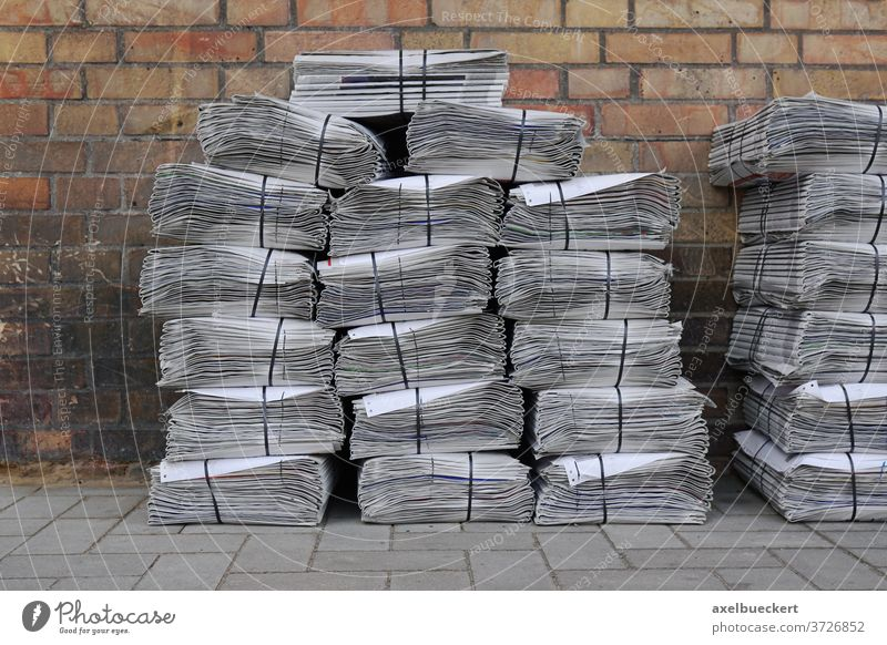 newspaper stack on street pile bundle bunch press media heap delivery piled stacked bundled bunched tabloid nobody sidewalk background footpath pavement