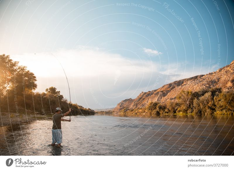 river fisherman with fishing rod sport person relaxation recreation nature lake angler reel people catch casting summer male fun water equipment one leisure