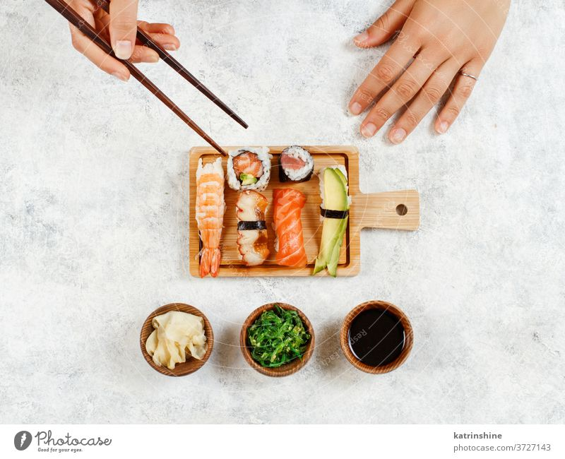 Top view of hand taking roll with chopsticks sushi ready to eat eating Sashimi Rolls sushi bar dinning Japanese Culture Seafood plate top view Asian Prawn Tuna