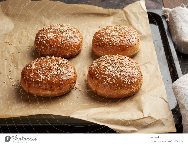 baked sesame buns on brown parchment paper, ingredient for a hamburger cheeseburger classic closeup crust delicious bakery bread breakfast eating fastfood flour