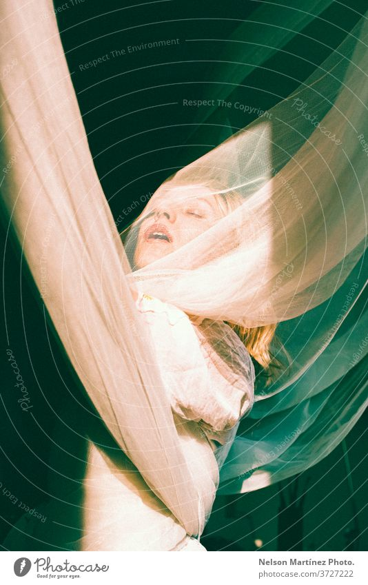 Portrait of a blonde woman. She is with open arms, wrapped in tulle curtains. bonde artist natural light freedom sensual portrait caucasian Portrait photograph