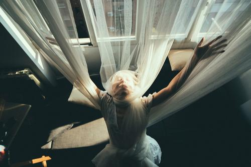 Overhead portrait of a blonde woman. She is with open arms, wrapped in tulle curtains. courtains natural light caucasian Portrait photograph pretty Beautiful
