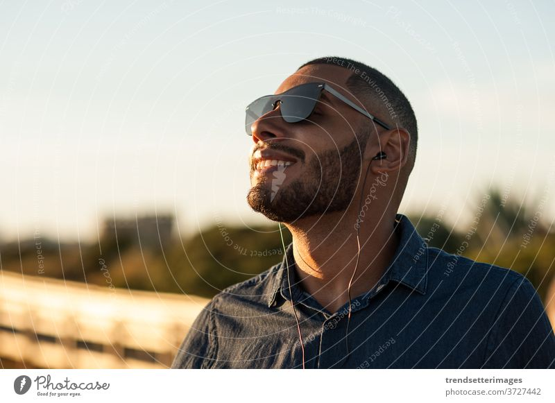 Latin man using earphones to listen music or motivational podcasts and enjoying the sunset meditation moutains vacation beach outside sunny mountains happy