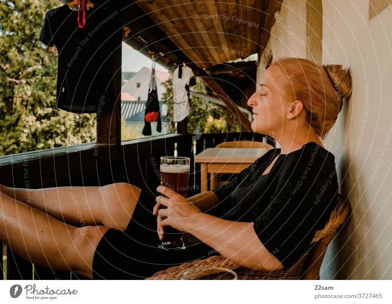 Young woman enjoying a wheat beer on the balcony enjoyment Drinking Beer white beer rest relax Dream Closed eyes Summer Sun Warmth Cycling cycling gear Garden