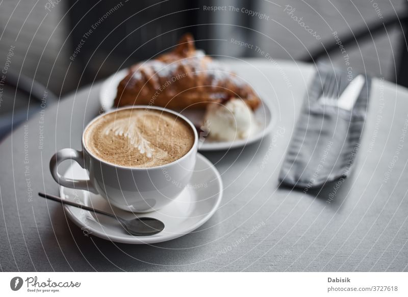 Cup of coffee and croissant on table in cafe breakfast coffee break drink morning cup espresso food bakery beverage brown caffeine fresh closeup hot wooden