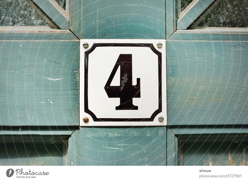 The number four is in black and framed on a square shield on the old blue wooden door 4 sign Number plate Old building front door Wooden door dwell