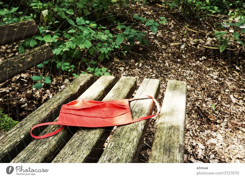 a red nose-mask lies on an old wooden bench in the forest Nose and mouth mask Mask Refusal Corona virus Risk of infection Respirator mask Wooden bench Face mask