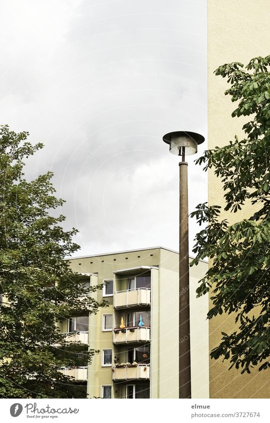 Holidays on balconies - view of a renovated modern apartment building with individually designed balconies, past a street lamp, a house wall and two trees