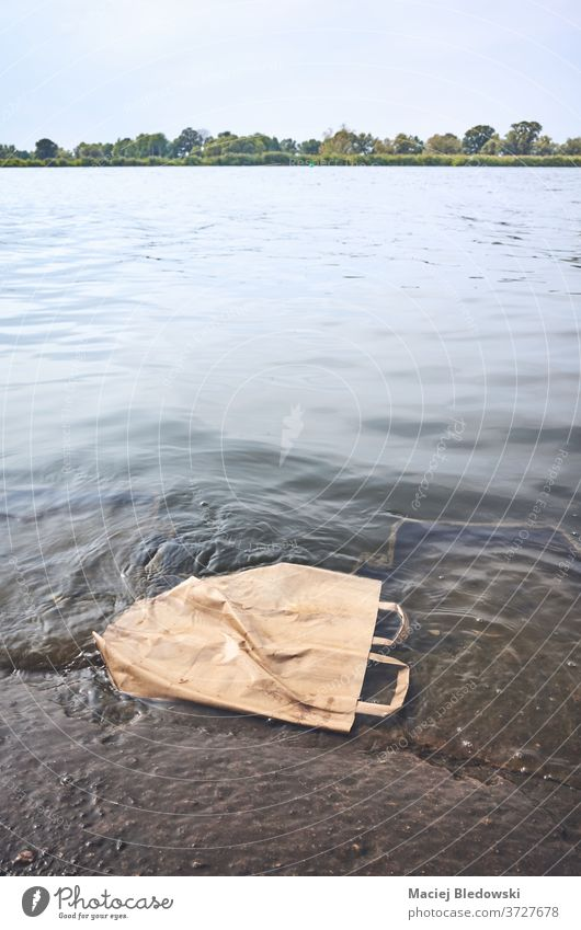 Discarded shopping paper bag in water. garbage recycling pollution recyclable environment trash nature litter environmental sea river recycle discarded problem