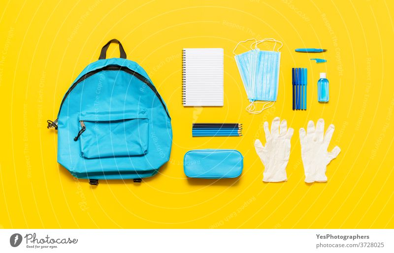 School supplies and backpack top view. Back to school in pandemic with protective masks back to school background blue concept copy space corona coronavirus