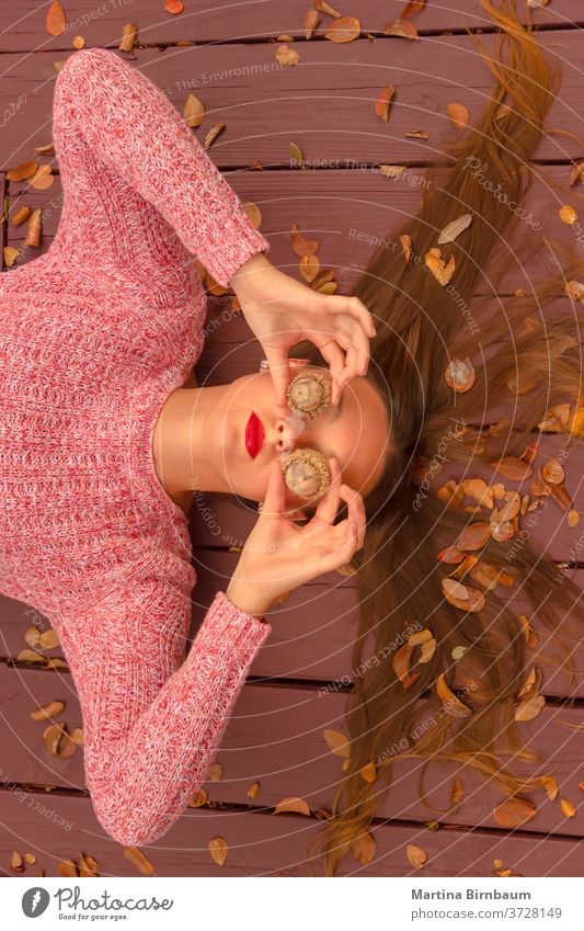 Where is fall ? Young woman lying on a wooden deck, covering her eyes with huge acorns. having fun model natural fashion face portrait leaf autumnal holiday
