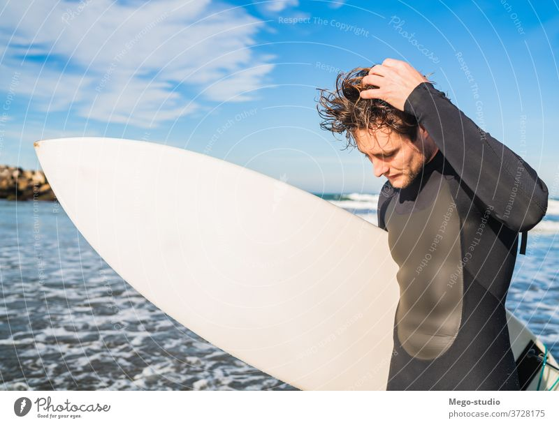 Surfer standing in the ocean with his surfboard. man water sport surfing sea surfer outdoors athletic coastline waves background adventure sports