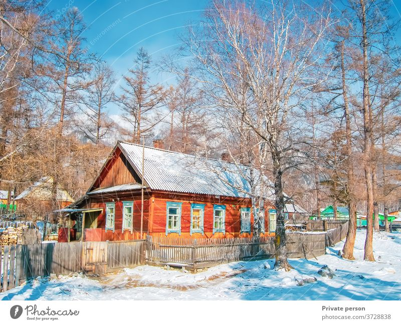 Picturesque wooden house in the forest on a sunny winter day. Snow, blue sky, mountains in the background. Healthy lifestyle concept, rural life. village white