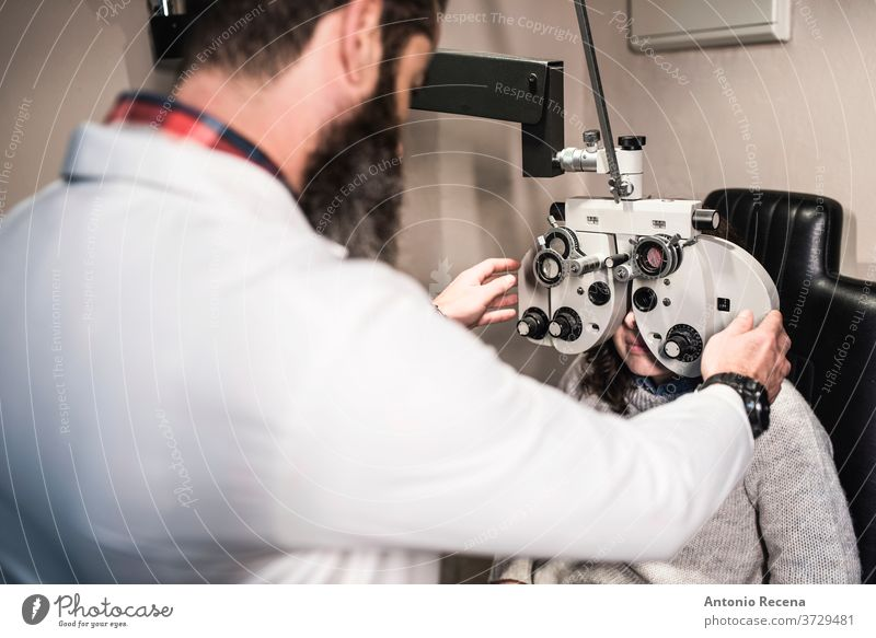 Bearded man working in optical store at work Slit lamp optics ophthalmology vision test bearded worker pharmacy person people optician oculist mid adult men