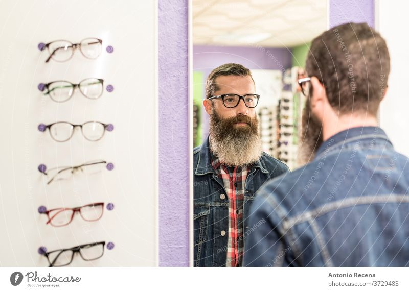 Bearded man working in optical store at work shop optician sunglasses customer buying beard handsome bearded trying on lenses vision oculist sight