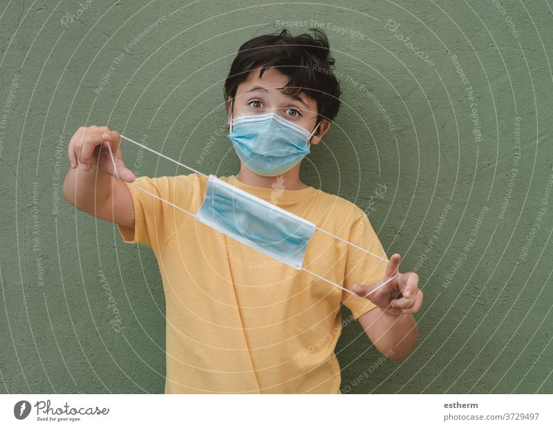 kid wearing medical mask holding a protective medical mask coronavirus epidemic pandemic quarantine child covid-19 symptom medicine health positive test