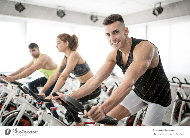 Group of people in spinning gym room exercise bike fitness men adult side view sweat muscle toning muscular build horizontal body care spanish color image