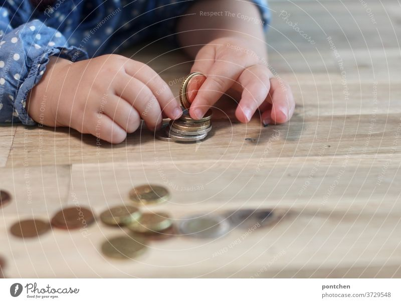 Child plays with coins and sorts them. Child's play, curiosity, pocket money Coin Cent children's hands Children's game Money finance child benefit family money