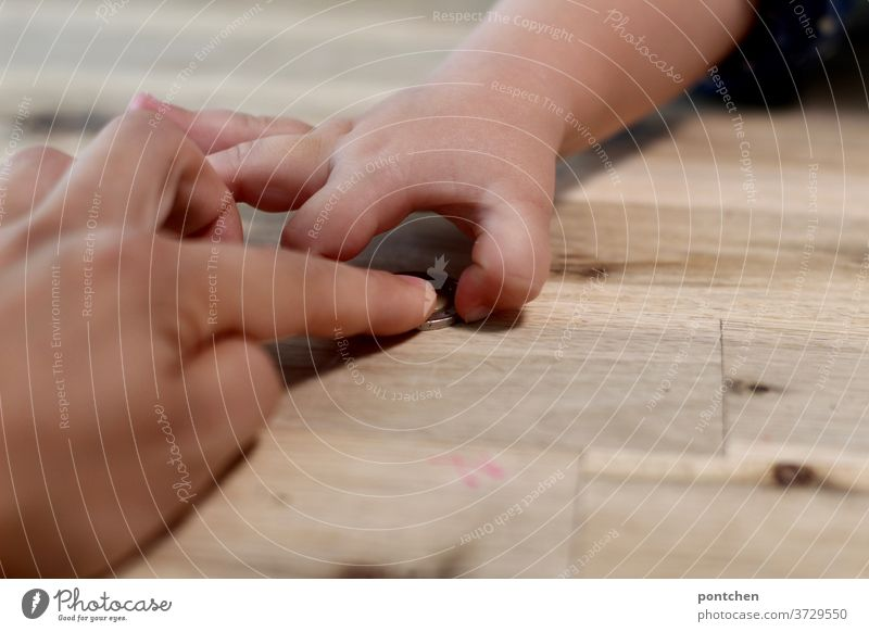 One hand gives, the other takes. Mother slides a coin over the wooden table to her child. Money Coin Child Push Give Take Costs Expensive child benefit