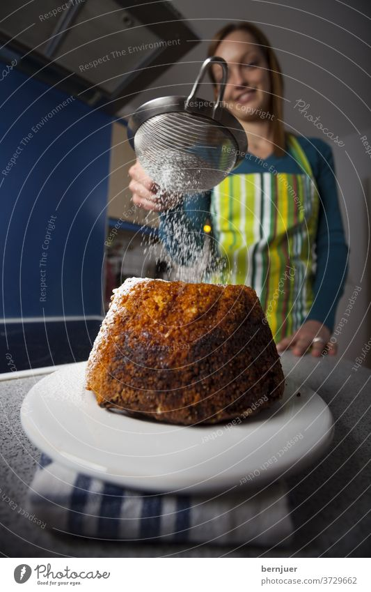 Woman with a bundt cake in a kitchen Gugelhupf Sweet Dessert Eating Sugar Delicious Cake background Nutrition feminine biscuits homemade sprinkle ready to eat