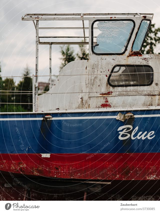 Blue - side view and bridge of an old motorboat in red and blue Old Red White Stern Rust corroded warehouse Boat storage Buck jacked up ship ship graveyard Oar