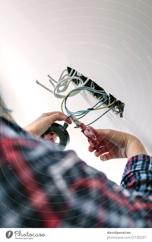 Unrecognizable electrician working on the electrical installation of a house unrecognizable electrical technician cutting cable danger scissors electric cable