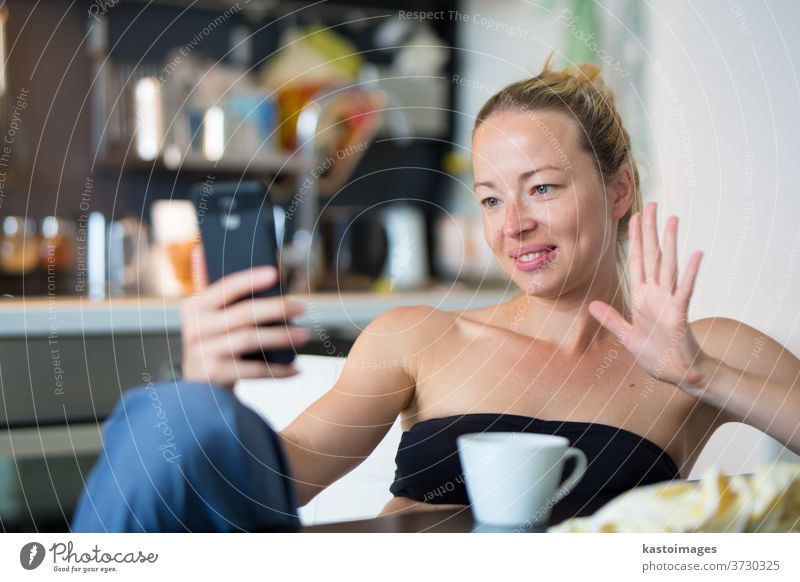 Young smiling cheerful pleased woman indoors at home kitchen using social media on mobile phone for chatting and staying connected with her loved ones. Stay at home, social distancing lifestyle.