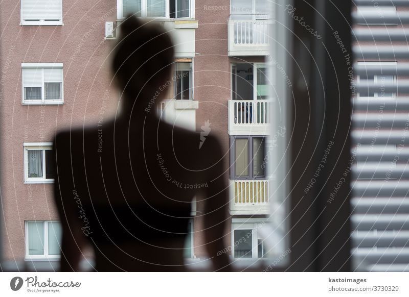 Home quarantine and social distancing during covid pandemic. Silhouette of lonley caucasian woman standing by window, anxiously looking out. Coronavirus infection, pandemics, disease outbreaks