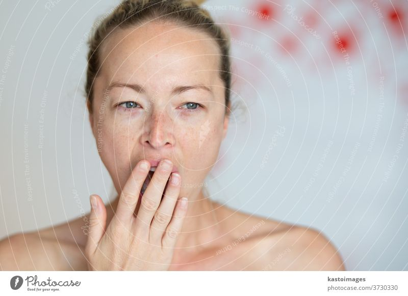 Closeup portrait headshot of sleepy young woman covering her wide open mouth while yawning by her palm. Face expression,emotion, body language concept. female