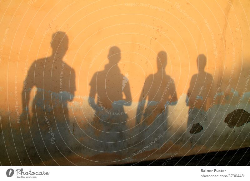 Shadow of four young men against a wall during sunset background dusk friends group group of friends outdoor people person shadow silhouette sunlight sunrise