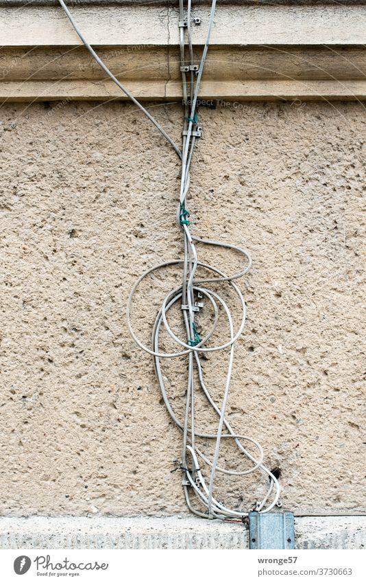 jumble of old cables on a house wall disorientation Muddled muddled Terminal connector Cable wires Telephone cable Colour photo Technology Chaos