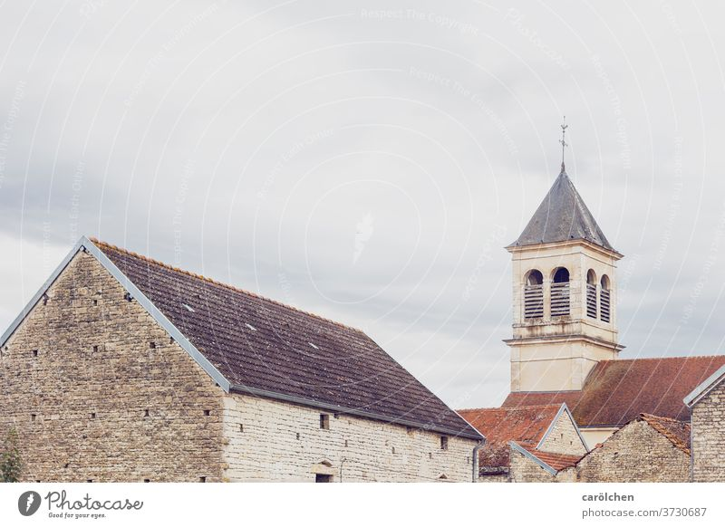 Village in the French countryside Church spire Roof roofs Wall (barrier) Covered Sky grey Dreary Simple unostentatious Calm Old town France