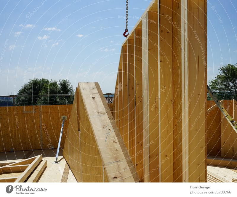 Timber construction site, a house wall is hanging on the crane Wooden house carpentry timber construction Construction site wood Colour photo Exterior shot