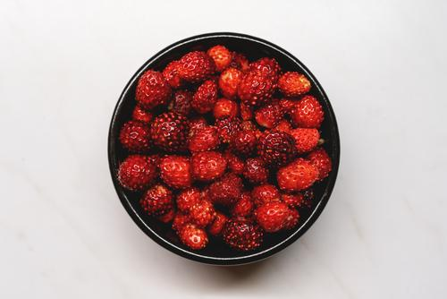 Top view of fresh ripe dark red wild strawberries in a black bowl on a white background strawberry fruit sweet top view healthy summer dessert delicious organic