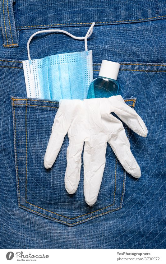 New normal in pandemic concept. Medical mask, hand sanitizer, and gloves in jeans back pocket avoidance back-pocket blue care close-up corona coronavirus