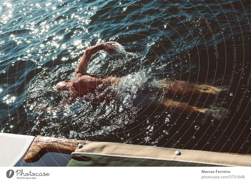 older man swimming in the sea next to his boat recreation calm outdoor european sailing activity exercise yacht tourism beautiful people vacation lifestyle