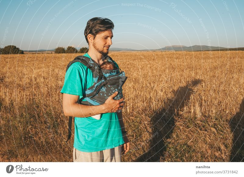 Single male parent carrying her baby with a backpack dad newborn front kangaroo single single parent family outdoors summer fall sunlight take a walk modern