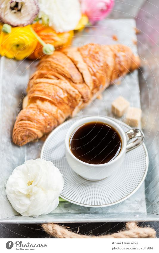 Fresh Croissant, Cup of Coffee and Ranunculus Flowers. Breakfast coffee croissant breakfast morning pastry cup white table ranunculus flowers drink tray
