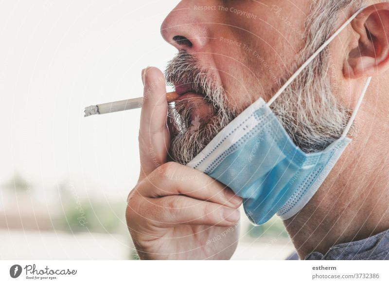 covid-19,man with medical mask smoking a cigarette at the street coronavirus 2019-ncov unhealthy smoke epidemic prohibition cancer protection clampdown habit