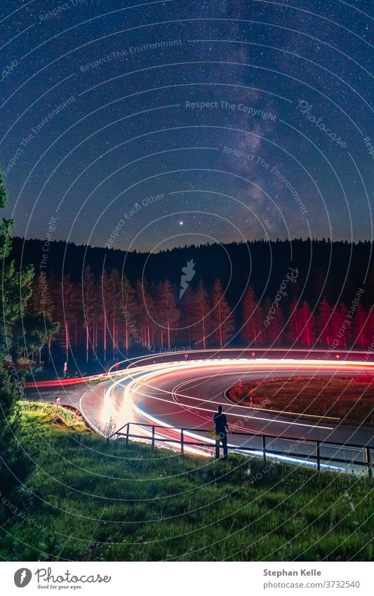 Milkyway, long exposure of a man standing at a railing in front of a curvy street, while cars are passing by and leave cartrail light. milkyway wonderful
