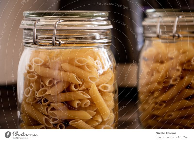 Uncooked penne pasta in glass jar iltalian food uncooked background kitchen italy lunch macaroni mediterranean italian nutrition raw tube vegetarian yellow
