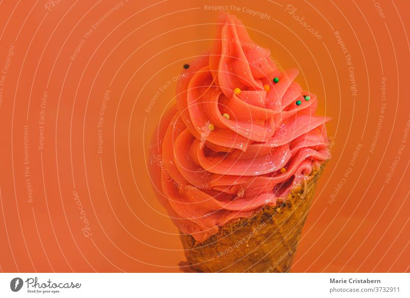 Pink colored ice cream in a cone against pastel background to show concept and colors of summer time summer colors summer food pink ice cream dairy isolated
