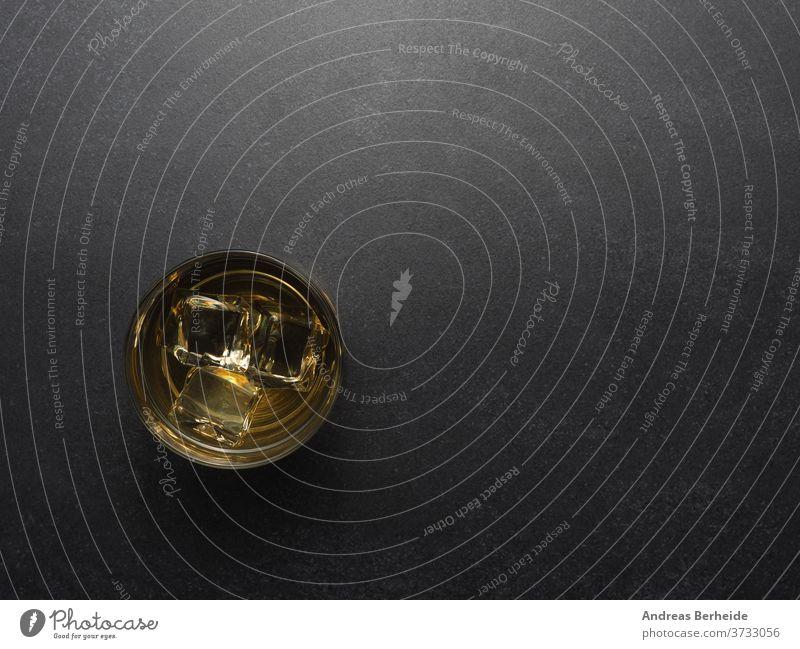 Glass of whiskey on a dark stone table whisky cold single rocks cube golden cognac scotch brandy vintage background liquid malt drink brown black copyspace